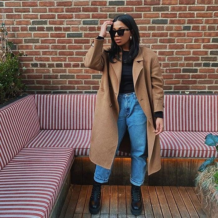 chica morena con lentes de sol y cabello largo usando un top negro, blazer oversized cafe jeans de tiro alto y botas negras de cuero