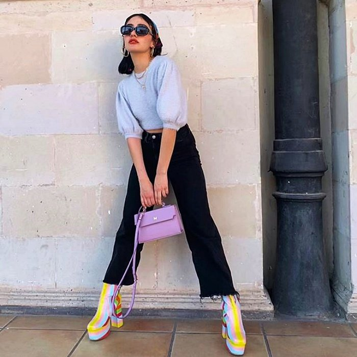 dark short hair girl with sunglasses, red lipstick, wearing a crop top sweater with black long shot jeans, pastel multicolored heels and lilac handbag