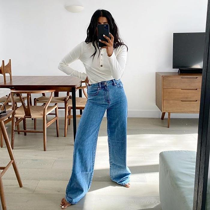 chica morena de cabello largo con top de manga larga blanco, jeans de tiro alto acampanados tomandose un selfie en la sala de su casa