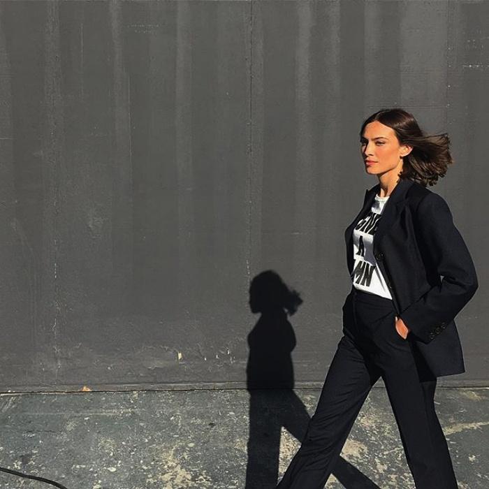 chica de cabello corto usando una camiseta blanca, saco negro y pantalones negros de vestir