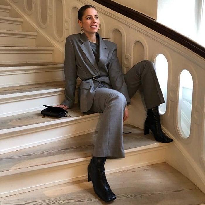 chica de cabello castaño con un saco gris, top gris, pantalones de vestir gris y botas negras de cuero