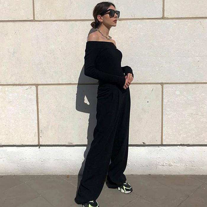 chica de cabello negro con lentes de sol usando un crop top negro de manga larga, pantalon de vestir negro