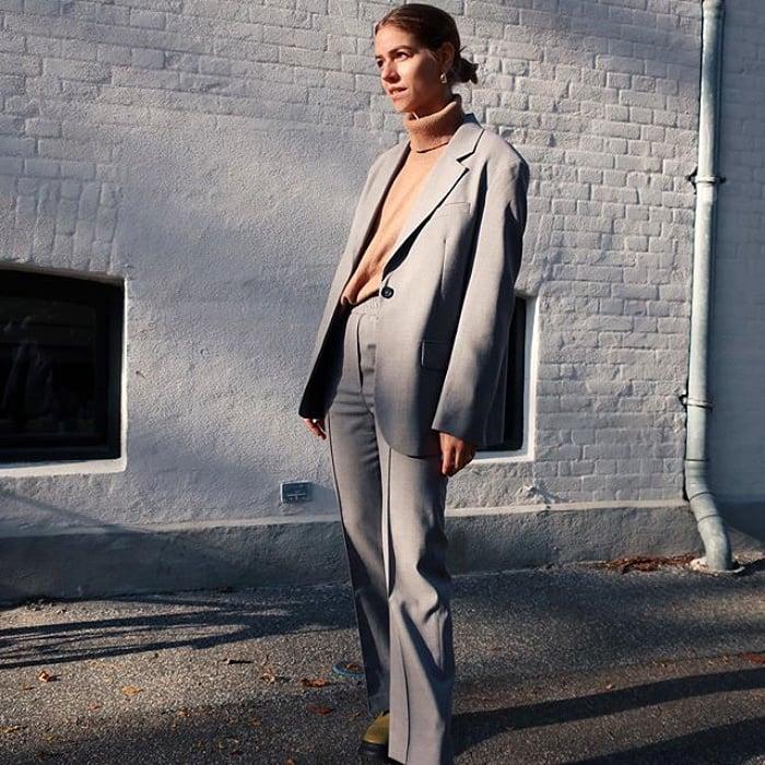 chica rubia usando un top beige, blazer gris y pantalon gris de vestir