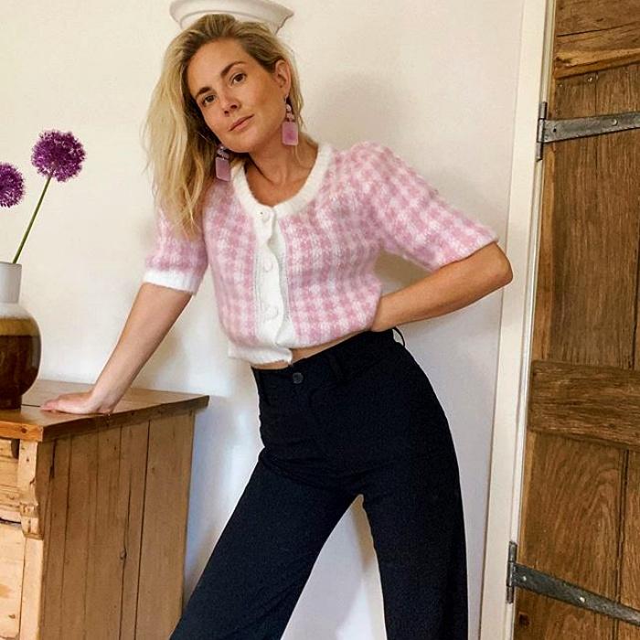 chica rubia con sueter rosa con blanco y pantalon de vestir azul marino