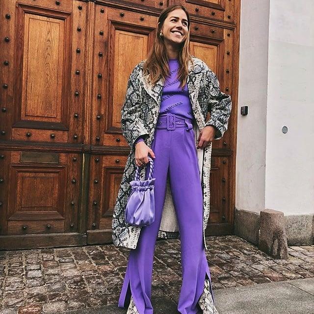 chica de cabello castaño con top morado, saco de animal print, bolso de seda lila, pantalones de vestir morados