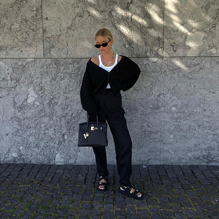 blonde girl with sunglasses, white tank top, black sweater and black dress pants