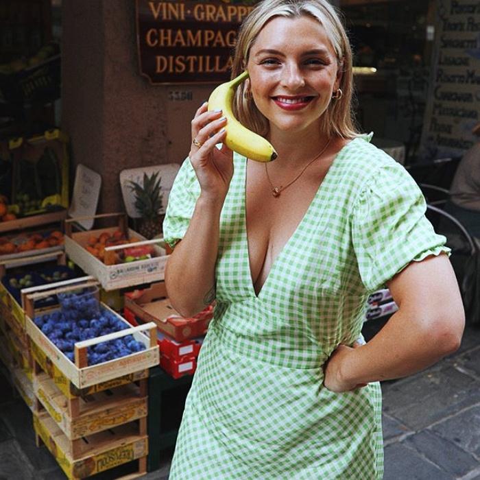 chica rubia con cabello corto usando un vestido verde claro con lunares blancos con escote en v