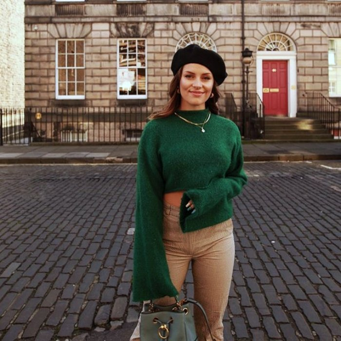 brown haired girl wearing a black beret, long green sweater and beige pants