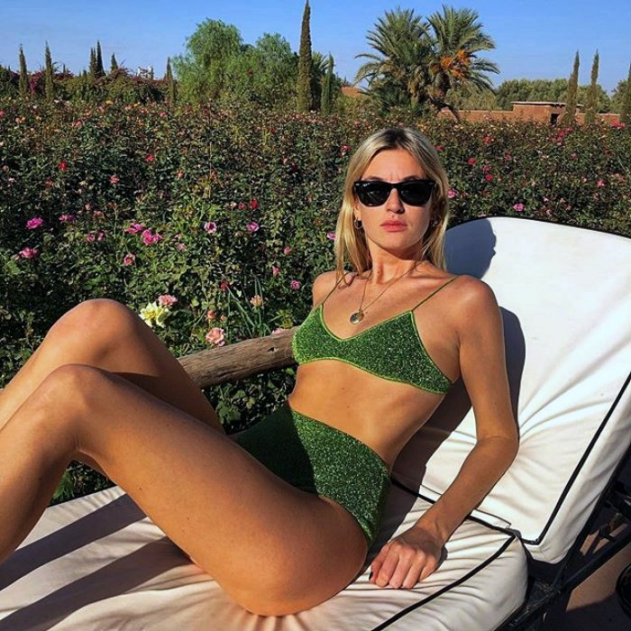 chica rubia con lentes de sol usando un bikin color verde