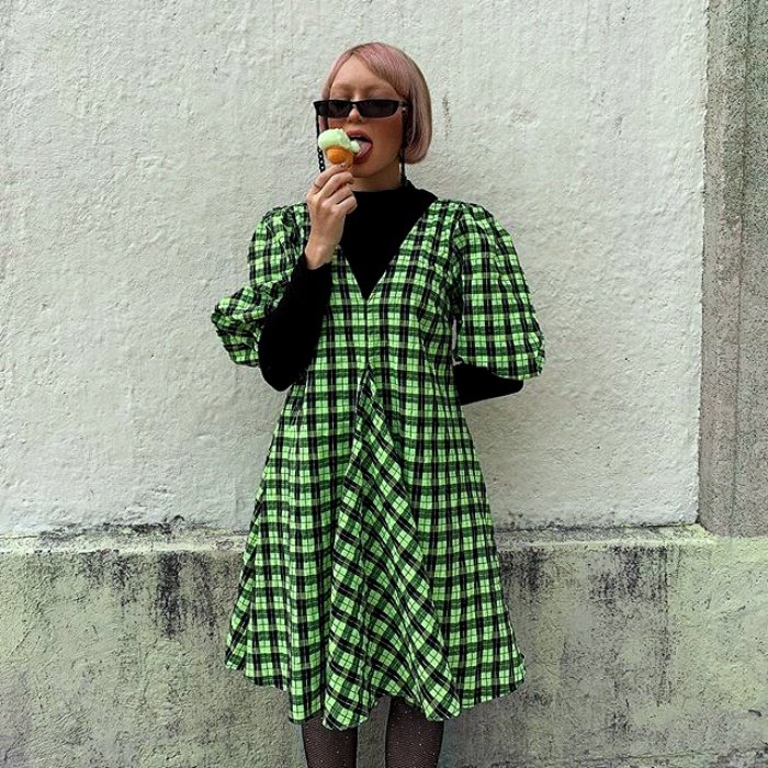 girl with short hair and sunglasses, wearing a black long-sleeved top with a green dress with white plaid eating ice cream