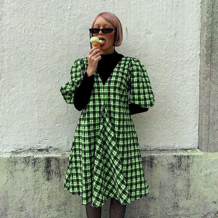 chica de cabello corto y lentes de sol, usando un top de manga larga negro con un vestido verde con cuadros blancos comiendo helado
