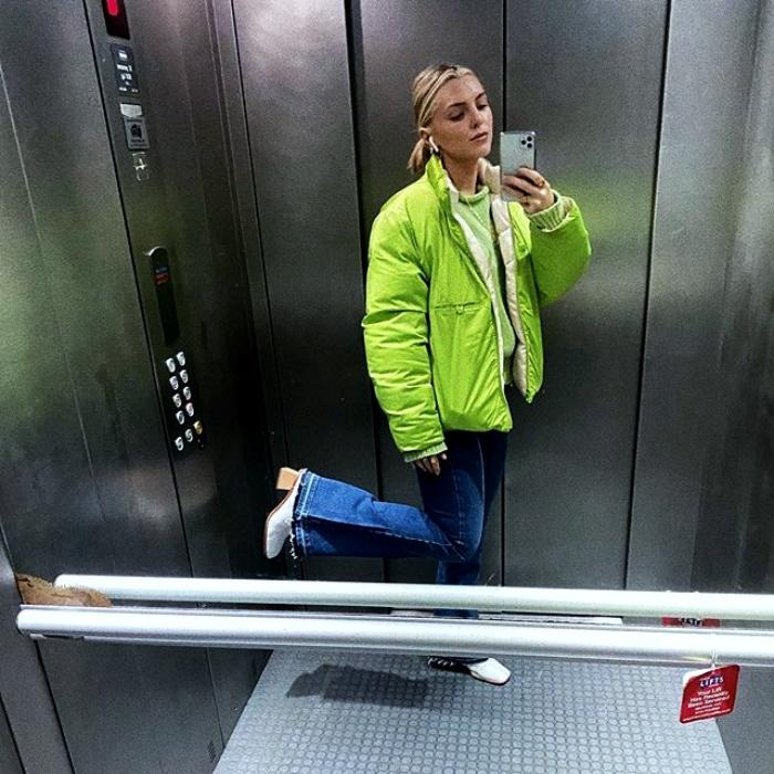 chica usando una chamarra color verde neón con jeans acampanados, botas blancas de tacon