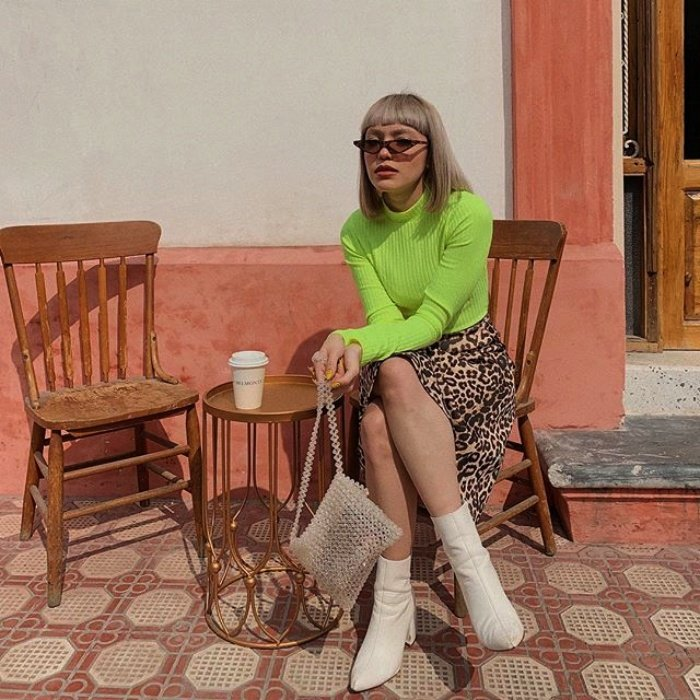 short-haired girl with sunglasses, neon green long-sleeved t-shirt, floral skirt and white boots sitting having a coffee