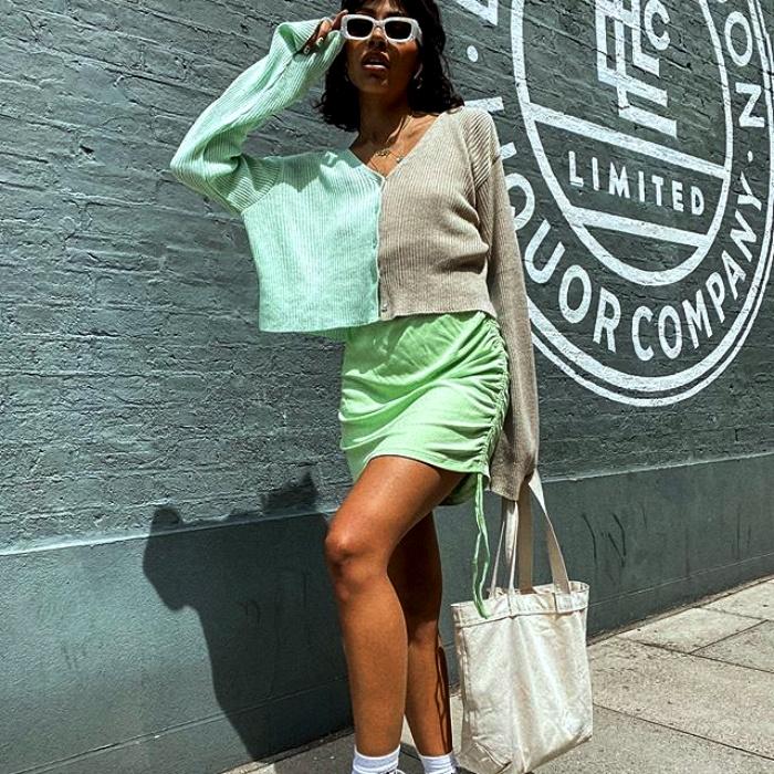 chica morena usando lentes de sol blancos con sueter de dos colores verde menta y gris, usando falda verde de satén y tenis deportivos blancos