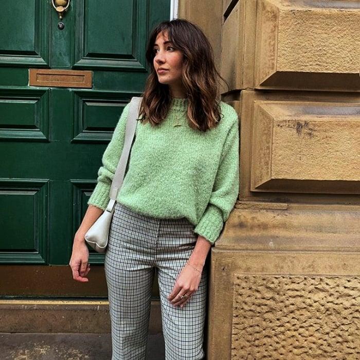chica de cabello castaño con suéter color verde pastel, pantalones grises y bolso blanco