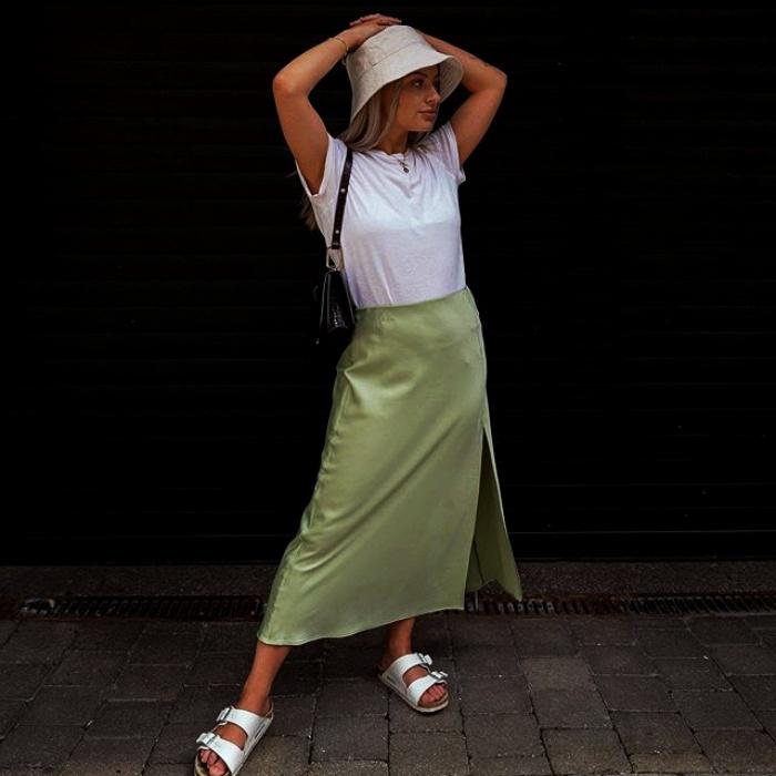 chica rubia con un bucket hat blanco, playera blanca de manga corta, falda de satén verde claro y sandalias blancas