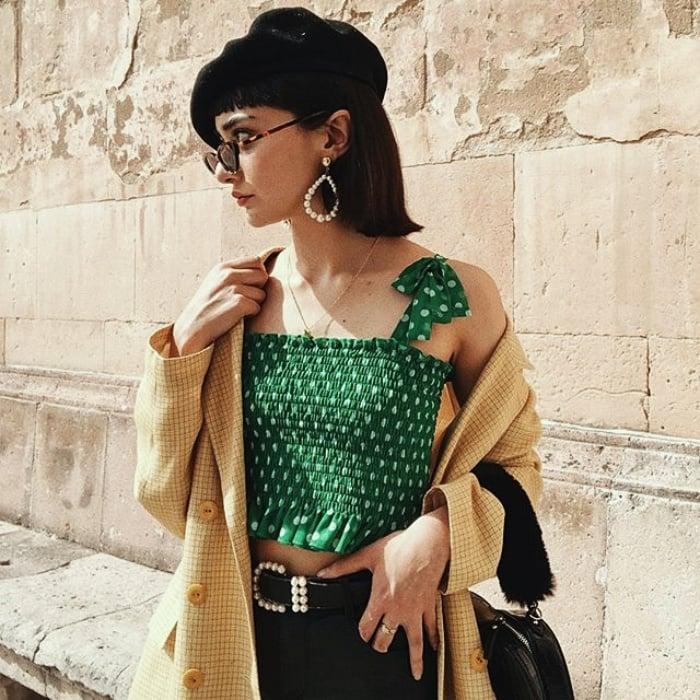 chica de cabello castaño corto usando una boina negra, lentes de sol, top de tirantes color verde esmeralda con puntos blancos, suéter beige, pantalones negros y cinturon con hebilla plateada