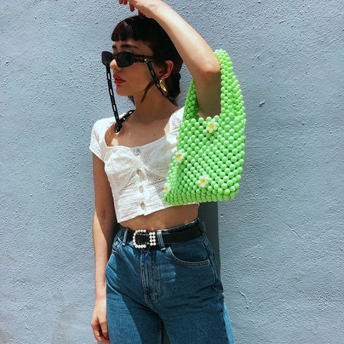 girl with black hair, sunglasses wearing a white short sleeve top, highwaist jeans and a green beaded handbag