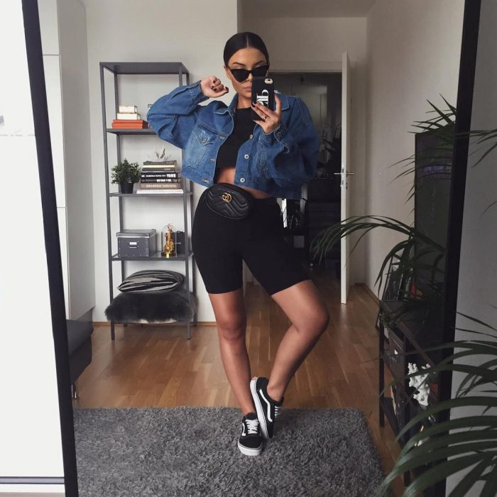 Girl with clinging hair in a sweater takes a selfie in front of the mirror with denim jacket and black cycling shorts