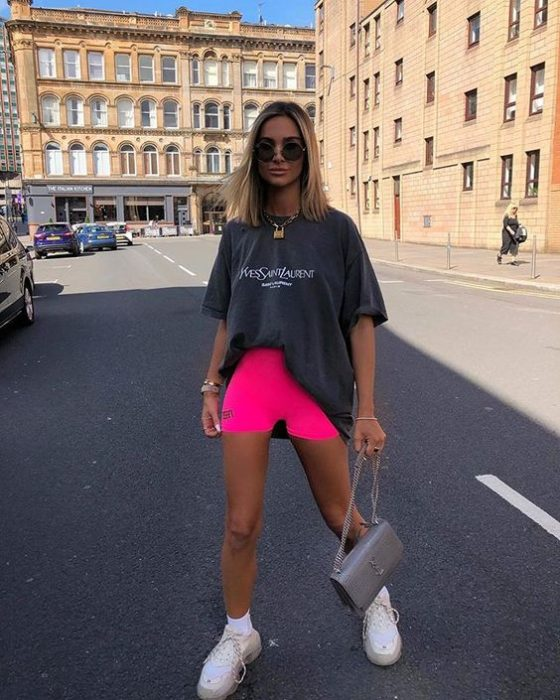 Blonde girl walking down the street in long gray blouse and neon pink cycling shorts