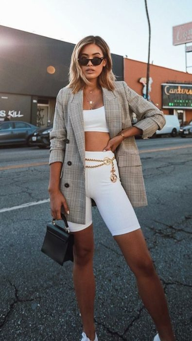 Long-haired blonde girl posing on the street with plaid jacket, crop top and white biker shorts with gold belt
