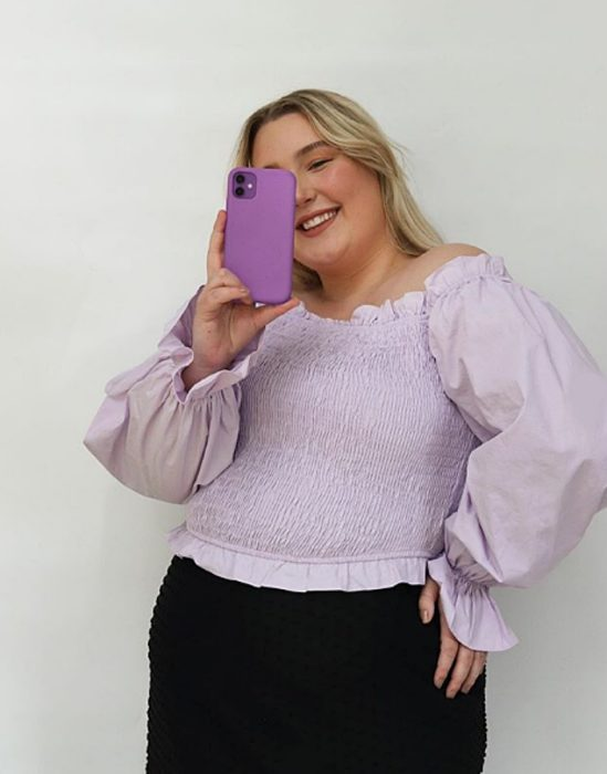 blonde curvy girl wearing a light lilac blouse and black jeans