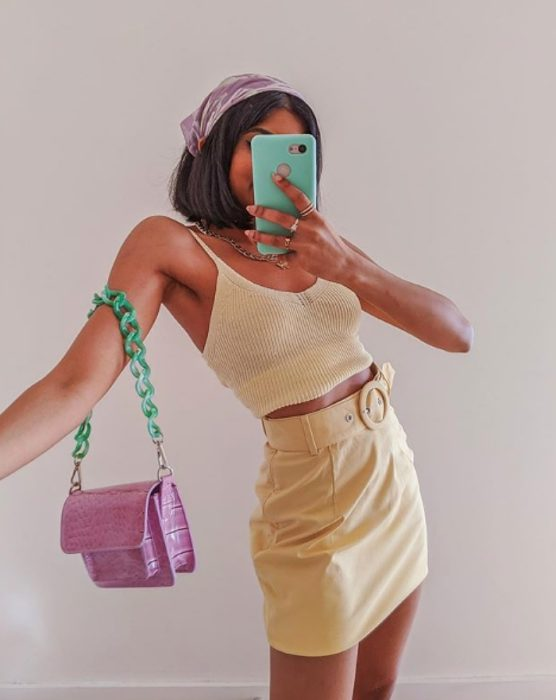 Dark-skinned girl wearing a light yellow top and skirt, a lilac bag with mint green and a scarf in her hair