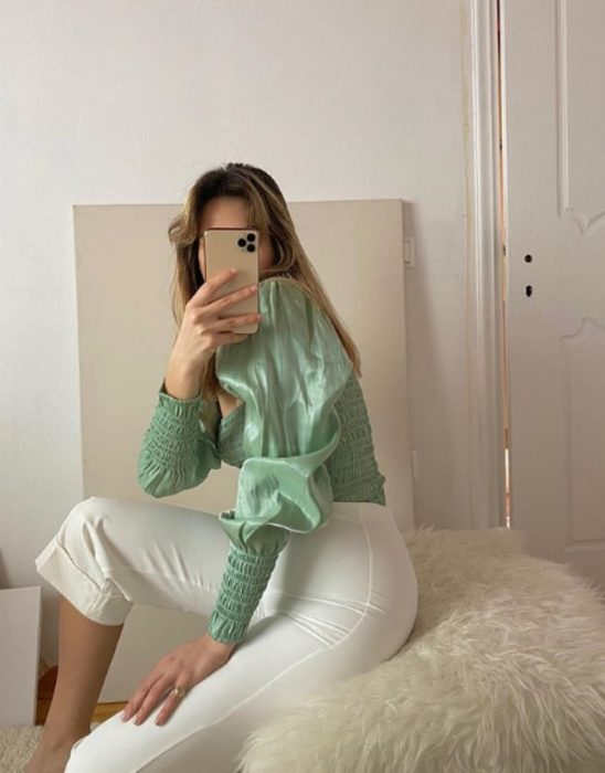 girl taking a selfie wearing a pistachio or mint green long sleeve top with white shorts