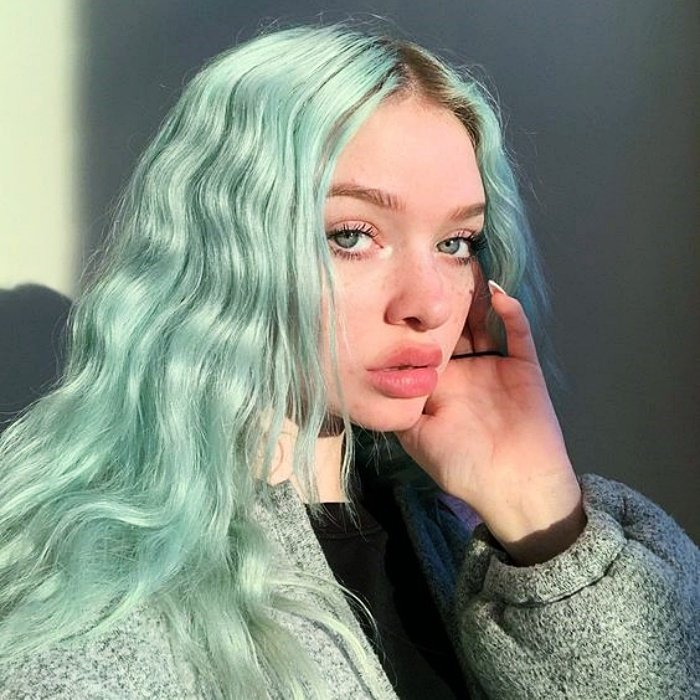 girl with long wavy hair dyed in mint or mint green hair