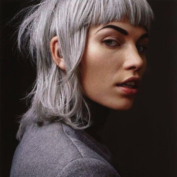 chica morena con cabello color plateado o gris, con fleco