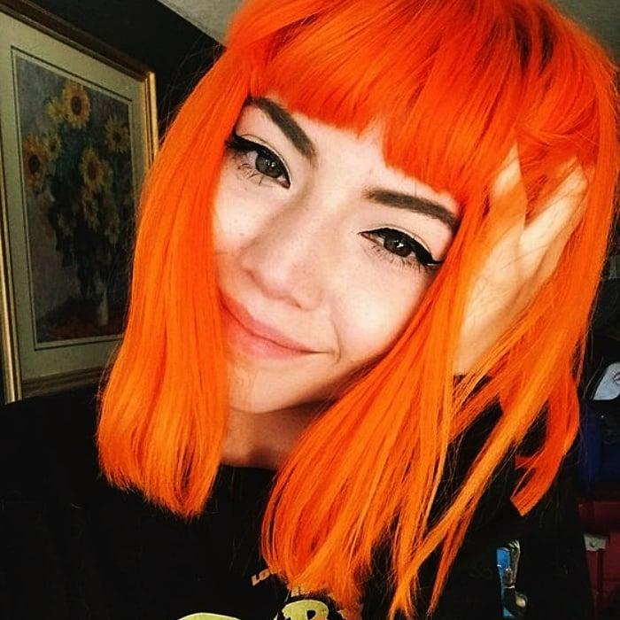 chica con cabello corto y fleco teñido en color anaranjado, naranja neon brillante