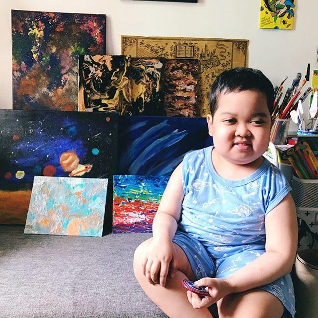 Aeden pio posando con algunas de las pinturas que ha hecho