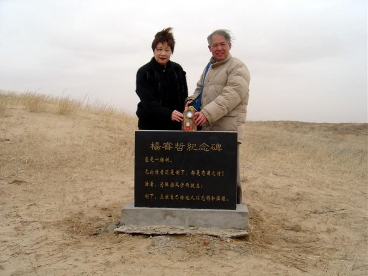 Padres de Yang detrás de una lapida en su honor sobre el área que reforestarian