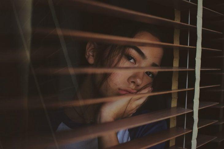 Chica mirando por la ventana, detrás de una persiana
