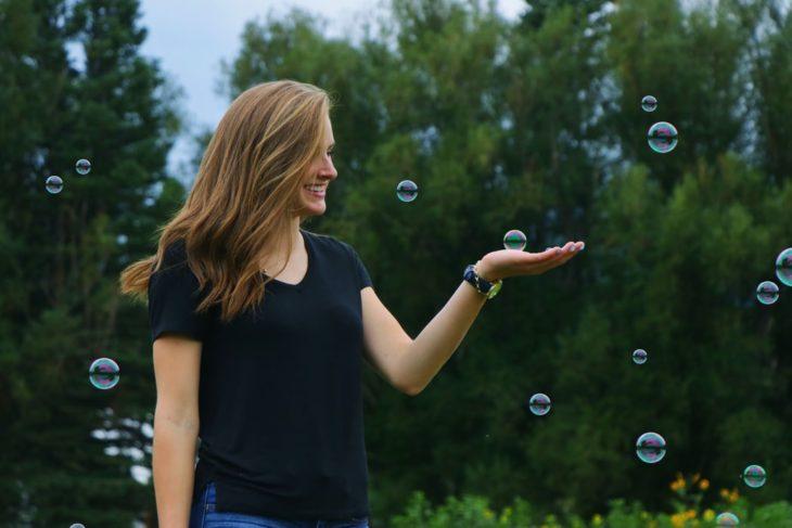 Chica sonriendo tocando las burbujas