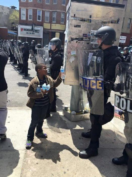Niño entrega botellas de agua a policías que llevan horas bajo el sol