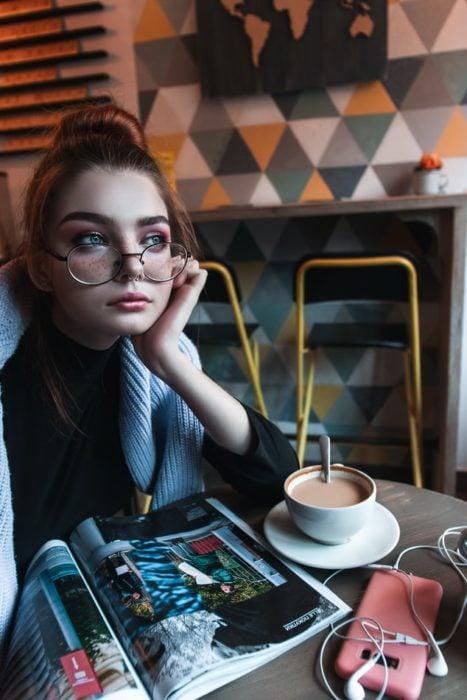 Chica sentada, tomando un café