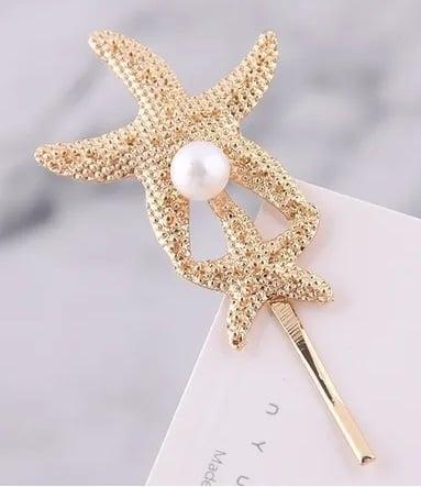 Pasador en forma d estrella de mar con una perla blanca