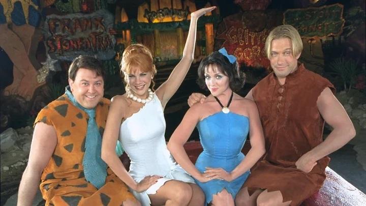 Escena de la película Los Picapiedra en Viva Rock Vegas con Pedro, Betty, Vilma y Pablo sentados en un bar