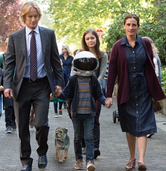 Escena de la película Extraordinario donde aparecen los padres de auggie y él usando un casco de astronauta