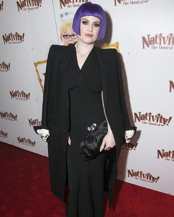 kelly osburne con el cbaello lila, y usnado outfit negro, en una alfombra roja