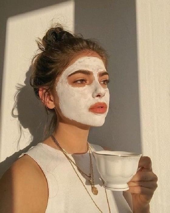 Chica tomando té mientras su mascarila actua