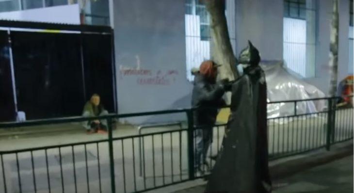 Batman solidario entregando comida a personas en situación de calle