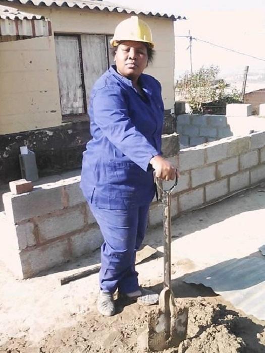 Zamanzini Philisiwe preparando mezcla para continuar construyendo