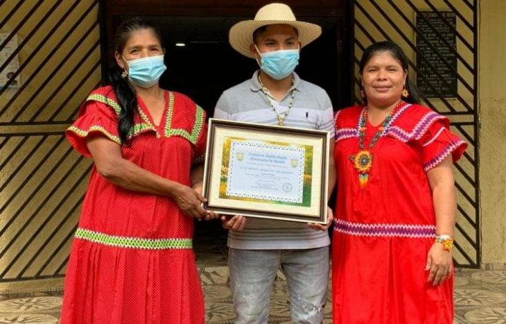 Luis Ángel mostrando su diploma de egresado con su familia en la comarca de Panamá