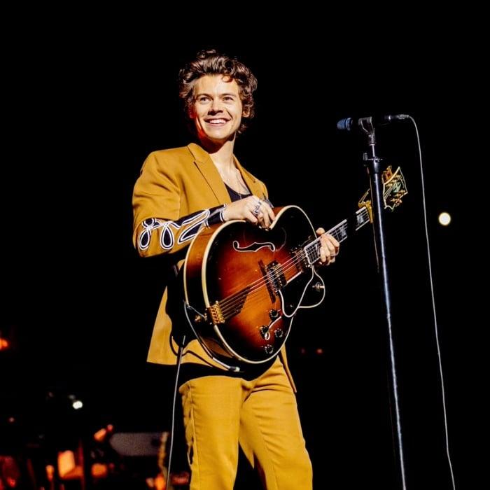 harry styles en traje amarillo con guitarra