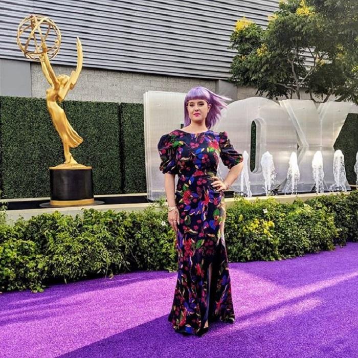 Kelly Osburne usando un vestido largo, en una alfombra morada