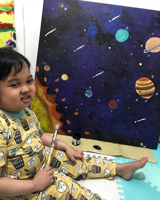 Eaden pintando un cuadro inspirado en el sistema solar