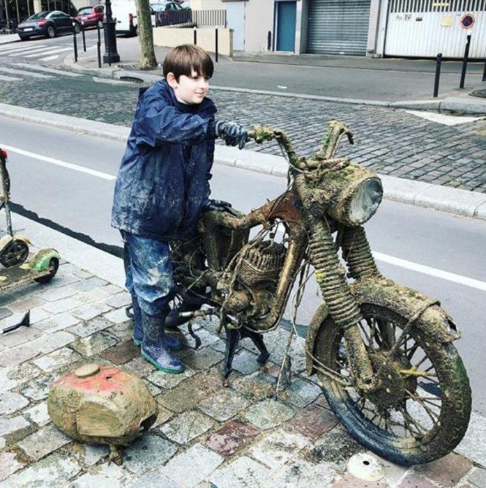 Raphaël moviendo una motocicleta que sacó del río Sena