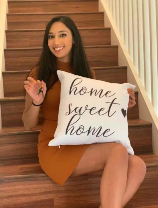 Pakeezah sentada en las escaleras de su casa con un cojín y las llaves de su hogar
